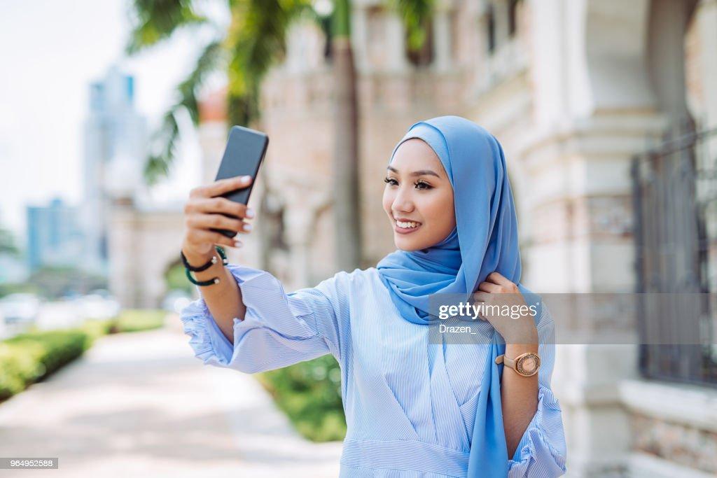 Portrait of Malaysian woman with hijab taking selfie : Stock Photo