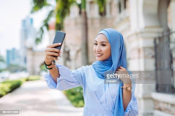 retrato de mulher da malásia com hijab tomando selfie - vestuário modesto - fotografias e filmes do acervo