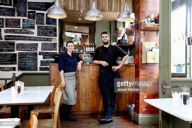 Portrait of male and female baristas leaning on counter of independent coffee shop