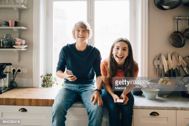 portrait of male and female friends with mobile phones sitting at kitchen counter - 14歳から15歳 ストックフォトと画像