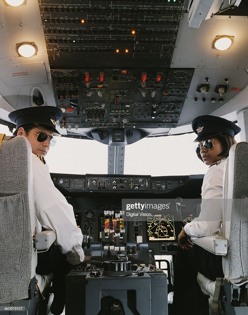 Portrait of Male and Female Pilots Sitting in the Cockpit : Stock Photo