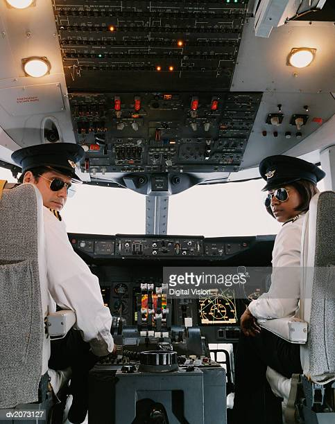 portrait of male and female pilots sitting in the cockpit - co pilot stock photos and pictures