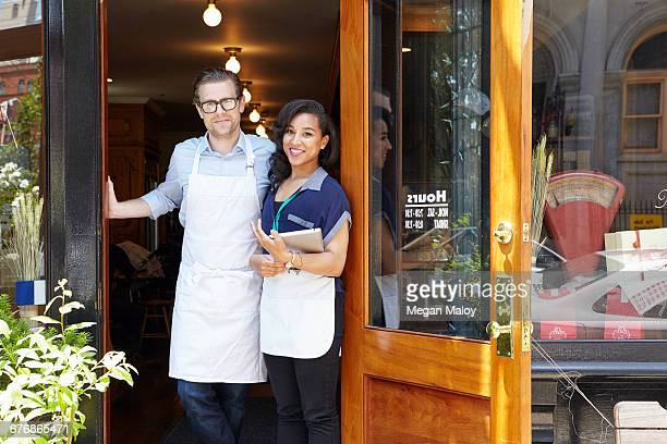 Portrait of male and female workers in bakery, standing in doorway