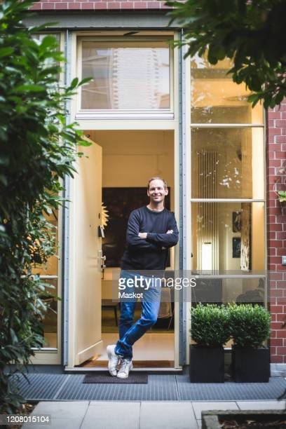 portrait of male architect standing with arms crossed at house entrance - einzelner mann über 40 stock-fotos und bilder