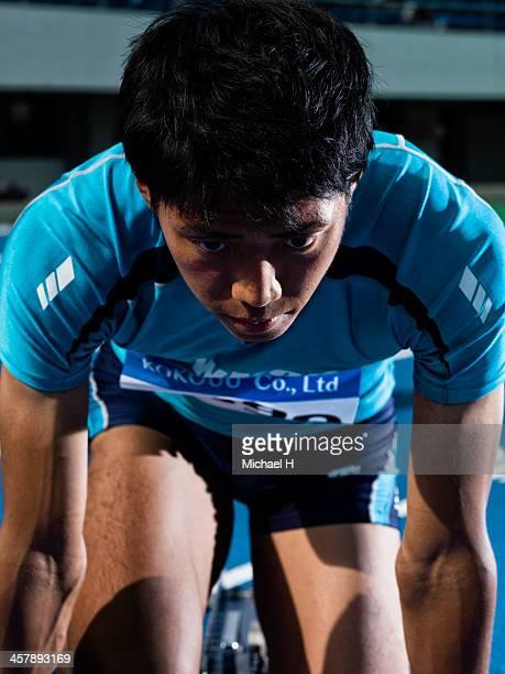 portrait of male athlete in starting blocks - 集中 ストックフォトと画像