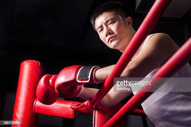 Portrait of male boxer resting his elbows on the ring side, low angle view