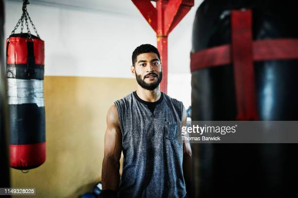 portrait of male boxer standing by heavy bag in boxing gym - sportswear stock pictures, royalty-free photos & images
