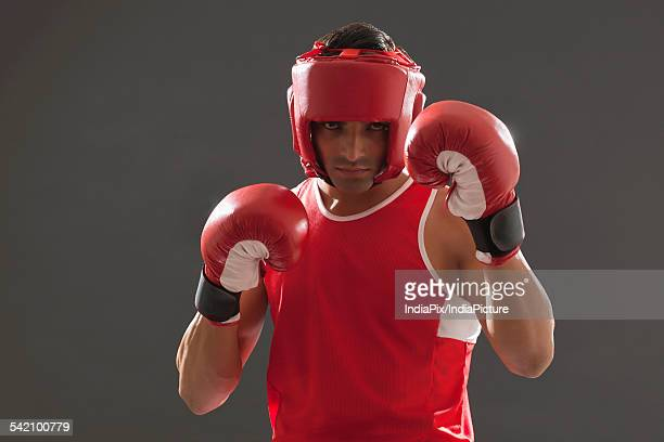 portrait of male boxer wearing head protector and gloves isolated over gray background - combat sport stock pictures, royalty-free photos & images