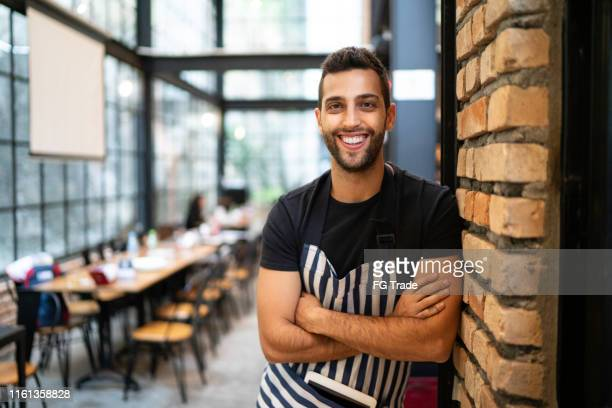 portrait of male business owner inside his restuarant - restaurant manager stock pictures, royalty-free photos & images