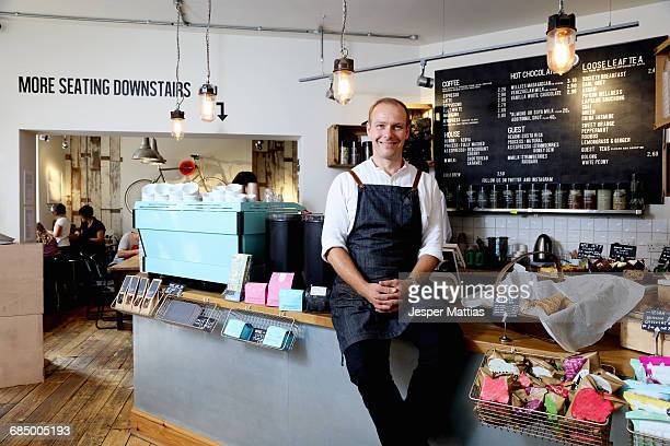 Portrait of male business owner sitting on counter of independent coffee shop