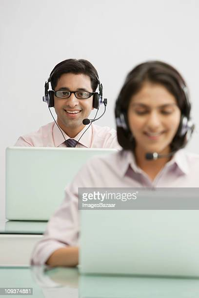 Portrait of male call centre worker using laptop, colleague in foreground