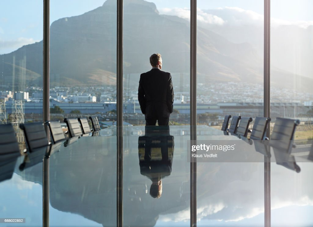 Portrait of male CEO in big corner office, looking out of window : Stock Photo