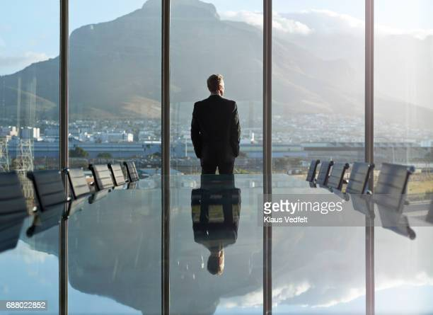 portrait of male ceo in big corner office, looking out of window - guardare in una direzione foto e immagini stock