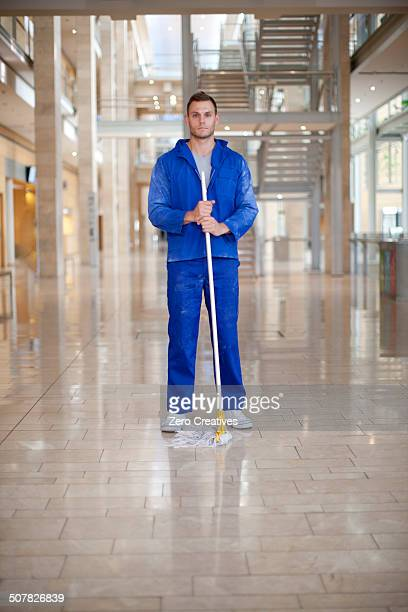 Portrait of male cleaner in office atrium