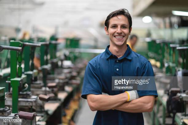 portrait of male cobbler at a shoe factory smiling at camera with arms crossed - shoe factory stock pictures, royalty-free photos & images