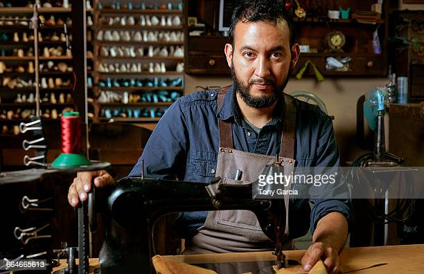 Portrait of male cobbler at sewing machine in traditional shoe workshop
