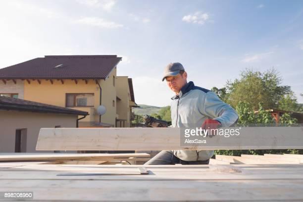 Portrait of male constructor building wooden chalet