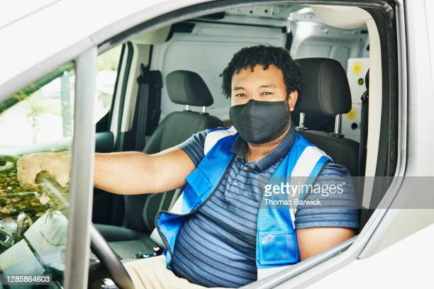 portrait of male delivery driver wearing protective face mask sitting in delivery van - essential workers stock pictures, royalty-free photos & images