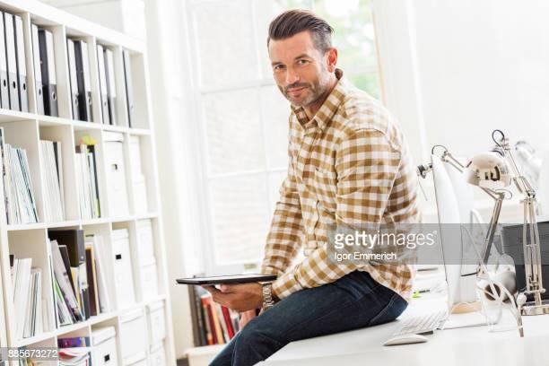 portrait of male designer sitting on desk in creative studio - homem 45 anos imagens e fotografias de stock