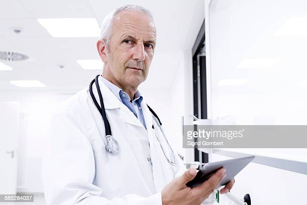 portrait of male doctor holding digital tablet - sigrid gombert stock pictures, royalty-free photos & images