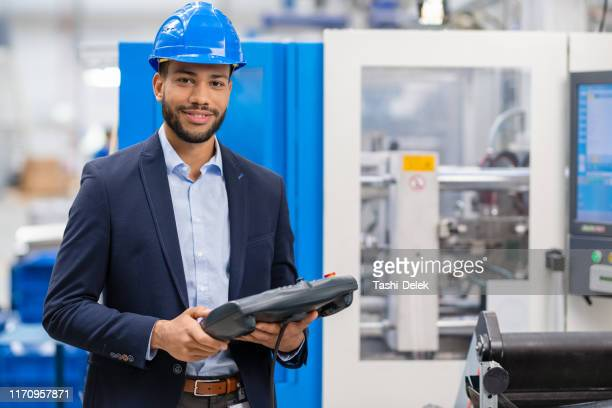 portrait of male engineer operating machinery in factory - director stock pictures, royalty-free photos & images