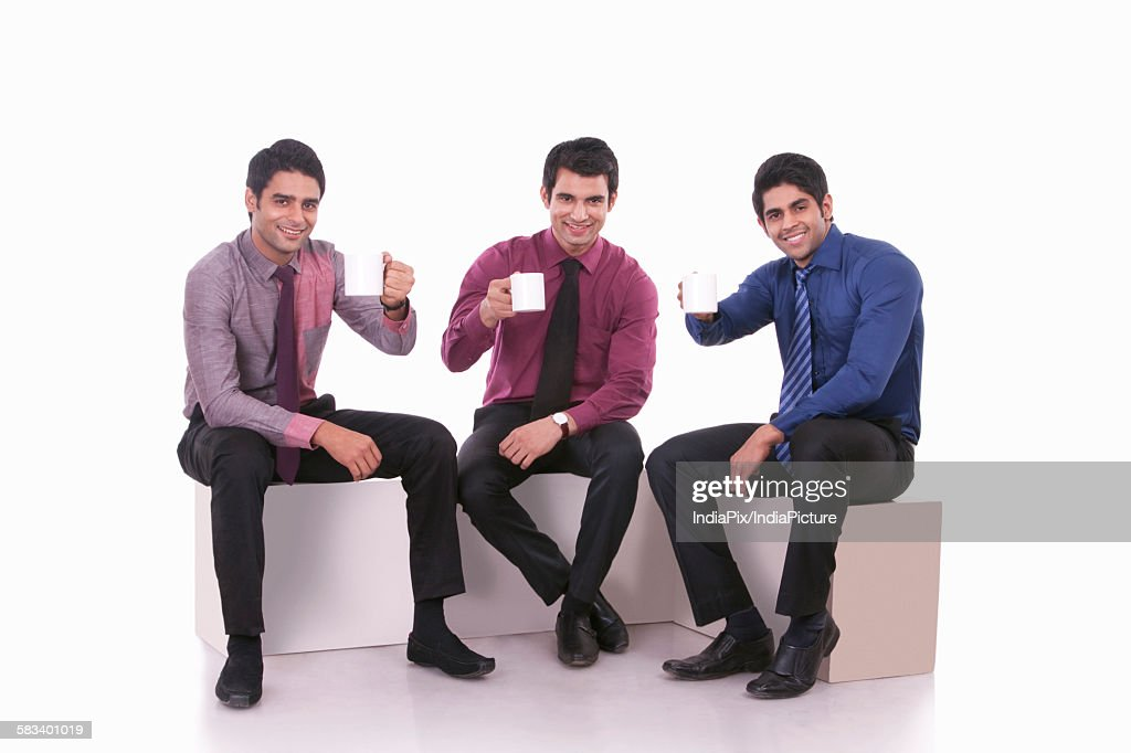 Portrait of male executives with mugs of tea : Stock Photo