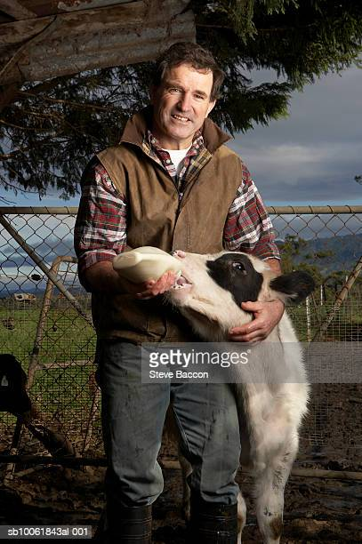 Portrait of male farmer feeding calf, smiling
