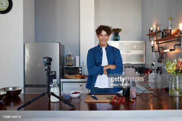 portrait of male food vlogger making video of blending a smoothie - blue film video stock-fotos und bilder