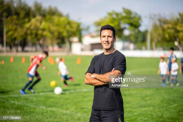 portrait of male footballer coaching mixed age players - coach stock pictures, royalty-free photos & images