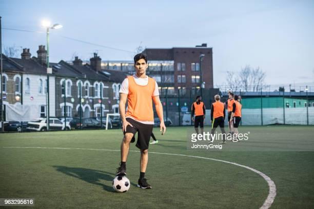 Portret van mannelijke voetballer op worp met voet op de bal en team mates in de achtergrond