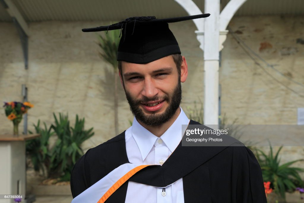 Portrait of male graduate wearing academic gown and mortarboard ...