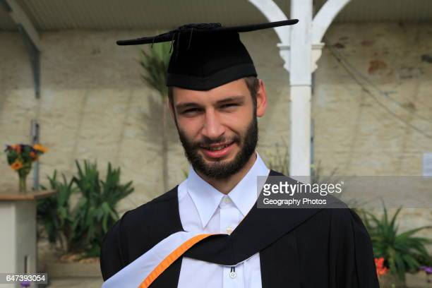 Portrait of male graduate wearing academic gown and mortarboard graduation ceremony University of Falmouth Cornwall England UK model released