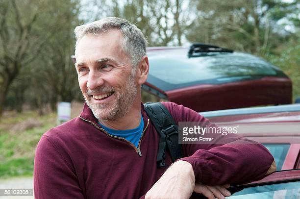 Portrait of male hiker leaning against car door