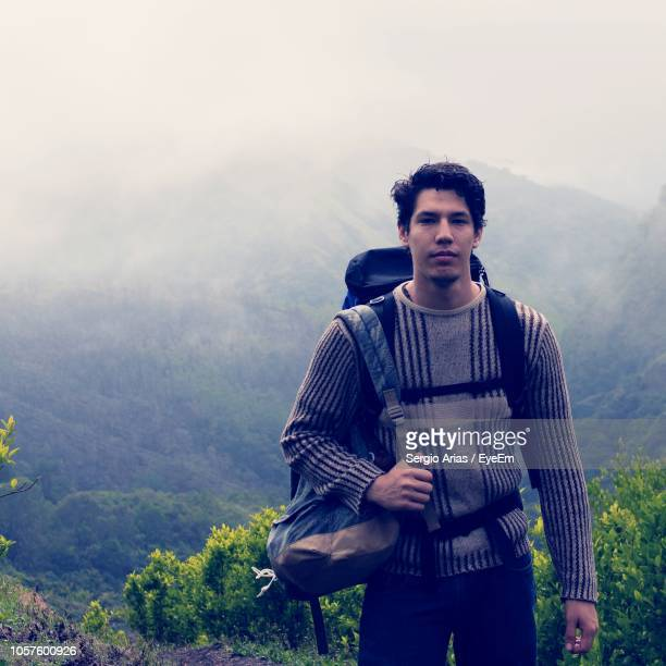 Portrait Of Male Hiker Standing With Bag Against Mountain