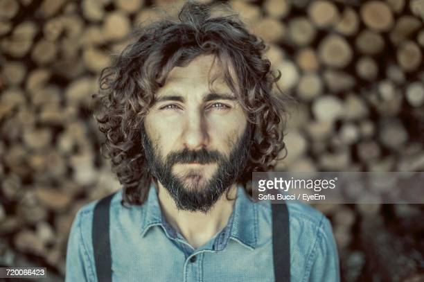 Portrait Of Male Hipster Against Firewood Stack