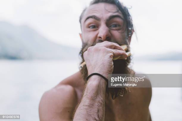 portrait of male hipster eating sandwich at lake como, lombardy, italy - macho stock-fotos und bilder