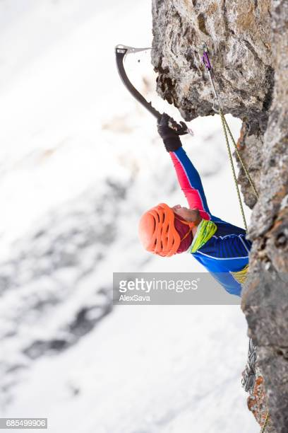 Portrait of male ice climber hanging on ice axe
