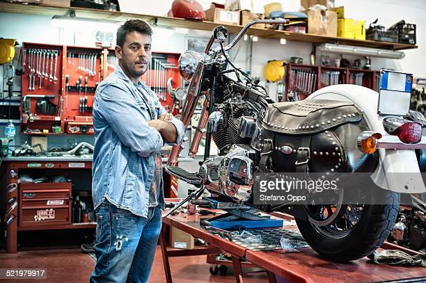Portrait of male mechanic with arms crossed in motorcycle workshop