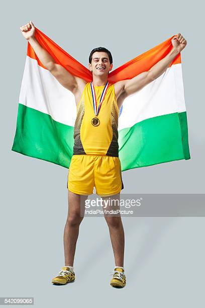 portrait of male medalist celebrating victory with indian flag against gray background - medalist stock photos and pictures