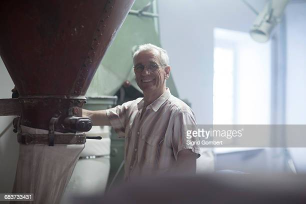 portrait of male miller monitoring milling machine at wheat mill - sigrid gombert stock-fotos und bilder