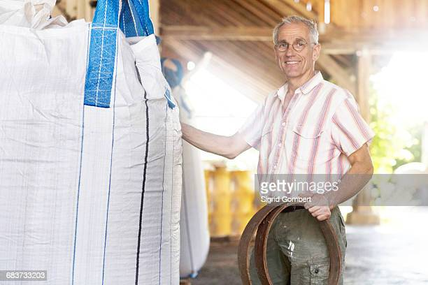 portrait of male miller with wholewheat sack in wheat mill warehouse - sigrid gombert fotografías e imágenes de stock