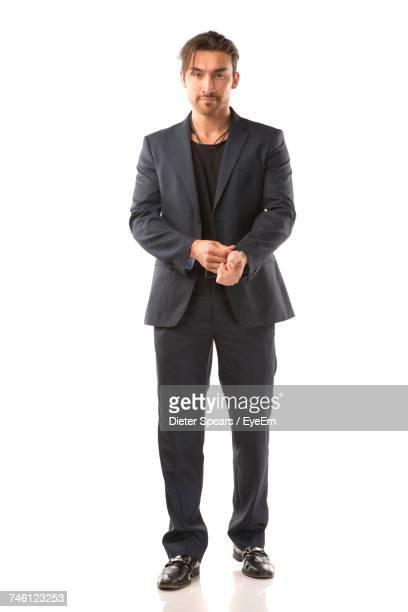 Portrait Of Male Model In Suit Standing Against White Background