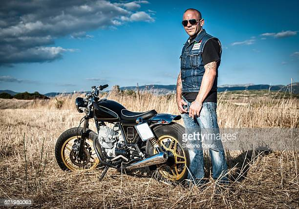 Portrait of male motorcyclist in plain landscape, Cagliari, Sardinia, Italy