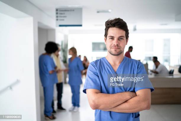 portrait of male nurse at hospital - male nurse stock pictures, royalty-free photos & images