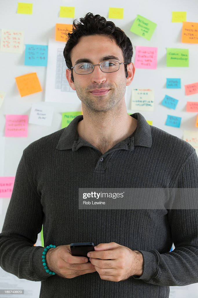Portrait of male office worker holding mobile : Stock Photo