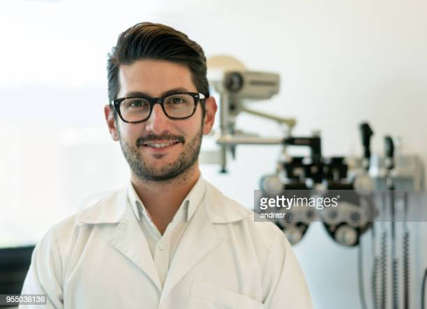 portrait of male opthalmologist looking at camera smiling and a phoropter at the background - eye doctor stock pictures, royalty-free photos & images