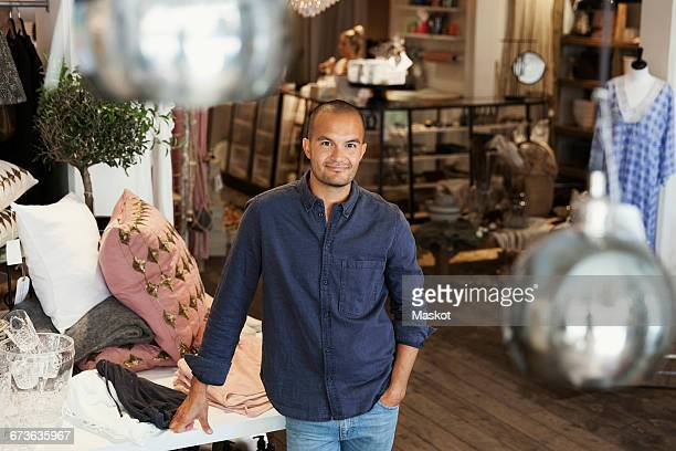 Portrait of male owner standing by clothes on table at store
