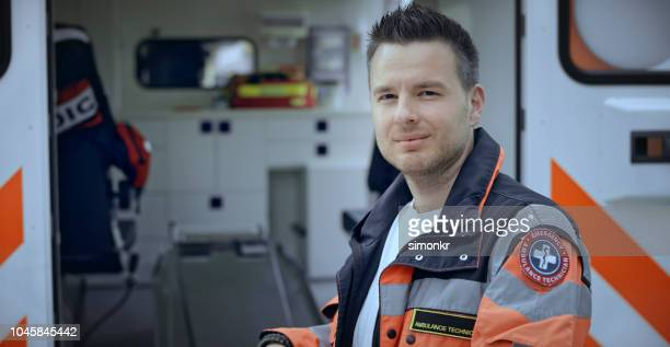 portrait of male paramedic standing next to ambulance - rescue services occupation stock pictures, royalty-free photos & images
