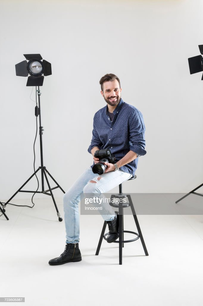 Portrait of male photographer sitting on white background in photographers studio : Stock-Foto