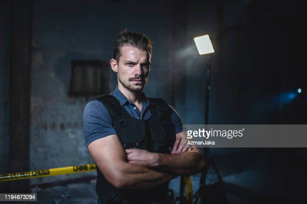 portrait of male police officer at urban crime scene - privateinvestigator stock pictures, royalty-free photos & images